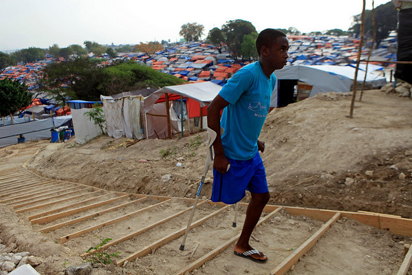 Mirtho Bellefleur, 21, whose right leg was amputated due to injures sustained in the earthquake, walks up from the makeshift camp set up in the Petionville Golf Club in Port-au-Prince, Wednesday, March 17, 2010. Two months after the quake, many homeless victims still have received no food and only 60 percent of the 1.3 million homeless have got plastic sheets or tents, according to U.N. coordinators of the massive but overwhelmed international relief effort. (AP Photo/Jorge Saenz)
