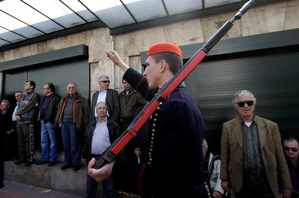 A member of Greece's presidential guard marches past striking taxi drivers outside parliament in Athens on Thursday, March 18, 2010. Taxi drivers and many petrol station owners went on strike to protest draft tax reforms, due to be finalized Thursday, which will force them to issue receipts. Greece's center-left government has pledged to hike taxes on the rich and force all Greeks to declare their full income, in a bid to fight rampant tax evasion and redress the debt-ridden country's finances. (AP Photo/Petros Giannakouris)