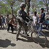 Spc. Sean Smith of Orlando, Fla. of the 1st Platoon 554th Military Police Company tries riding a bike belonging to village children near the end of a patrol Thursday, March 18, 2010, in the Koz Kunar district of Nangarhar province Afghanistan. (AP Photo/Julie Jacobson)