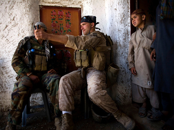U.S. Marine Lance Cpl. Mathew Gorzkiewicz, of North Liberty, Indiana, with the First Battalion, Sixth Marine Regiment, Alpha company, tries out an Afghan boy's sling during a patrol in Marjah, Afghanistan, Thursday, March 18, 2010. (AP Photo/Dusan Vranic)