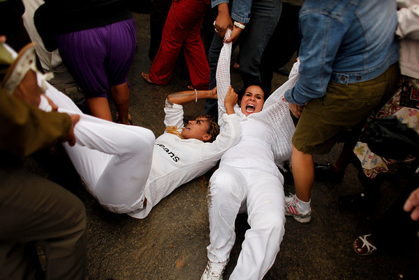 Member of the Ladies in White, a group of female dissidents, are removed from the street by security agents during a protest in Havana, Wednesday, March 17, 2010. Cuban security agents prevented Ladies in White from marching on the outskirts of the capital to demand the release of their jailed husbands and sons, physically removing them when they lay down in the street in protest. (AP Photo/Javier Galeano)