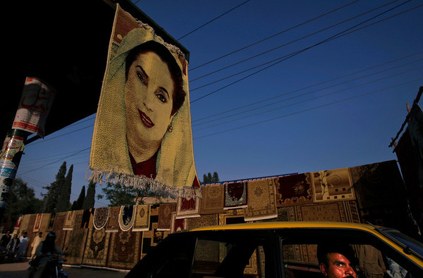 A Pakistani man, right, looks out of his car window while driving past a carpet bearing the image of Pakistan's slain leader Benazir Bhutto, displayed for sale along with other carpets on the side of the road in the old city of Rawalpindi, Pakistan, Wednesday, March 17, 2010. Dozens of people have been killed in Pakistan's largest city of Karachi including three found decapitated over the weekend in a wave of targeted attacks among rival political groups that some say is aimed at destabilizing the country's ruling coalition.(AP Photo/Muhammed Muheisen)