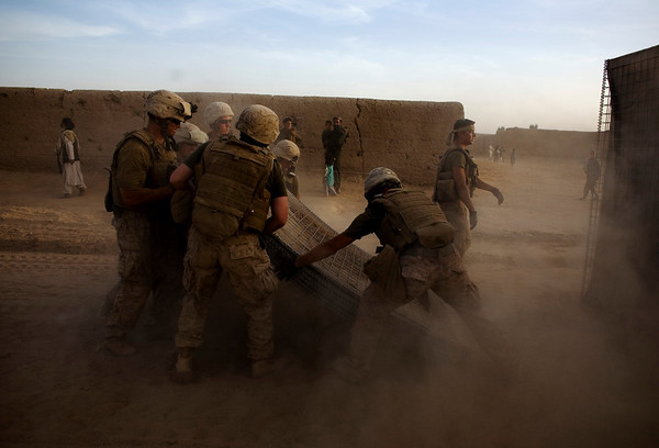 In this image taken Monday, March 15, 2010, in Marjah, marines of the First Battalion, Sixth Marine Regiment build a barrier around their base. Taliban insurgents are conducting a fear and intimidation campaign against residents of the southern Afghan town of Marjah, which international forces just wrested from insurgents. (AP Photo/Dusan Vranic)