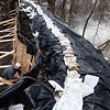Mark Houglum works on a 40 foot flood wall used to protect his Moorhead, Minn. residence from the swollen Red River on Thursday, March 18, 2010.  (AP Photo/Jay Pickthorn)