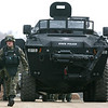 A law enforcement official walks out of an armored vehicle tank in a staging area in Hillsdale County, Mich. during a search for a fugitive who is part of a Christian militia group Monday March 29, 2010.  Nine members of a Christian militia group that claimed to be preparing to fight the Antichrist were charged Monday with plotting to kill a police officer and then slaughter scores more by bombing the funeral, all in hopes of touching off an uprising against the government. Eight members of the Michigan-based Hutaree were arrested over the weekend in raids in Michigan, Indiana and Ohio, and another was still being sought. (AP Photo/Madalyn Ruggiero)