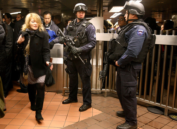 "A woman walks past two heavily-armed counterterrorism officers stationed outside the turnstiles at Grand Central Station in New York, Monday, March 29, 2010. The officers represent ""Operation TORCH,"" or Transit Operational Response with Canine and Heavy Weapons, funded by a grant from the Department of Homeland Security's grant to New York, Connecticut and New Jersey to help beef up 2,600 police officers who work for the New York Police Department's transit  bureau. New York's Metropolitan Transportation Authority beefed up security as a precaution Monday following the suicide bombing in Moscow's subway system. (AP Photo/Kathy Willens)"