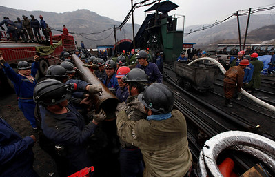 Rescuers unload metal pipes and pumping equipment onto a metal trolley  at Wangjialing coal mine in Xinagning, in north China's Shanxi province, about 650 kilometers (400 miles) southwest of Beijing,  Monday, March 29, 2010.  Rescuers working in a drizzling rain raced Monday to free 153 coal miners trapped deep underground by a flood that may have started when workers digging a new mine in northern China accidentally broke into a network of old, water-filled shafts.  (AP Photo/Gemunu Amarasinghe)