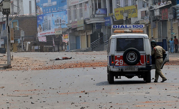An injured man lies on the road, left, after clashes in the old city area of Hyderabad, India, Monday, March 29, 2010. Authorities fired tear gas and warning shots and swung batons Monday to disperse crowds of angry Hindus and Muslims who attacked each other with stones and clubs in southern India, where more than 75 people have been injured.