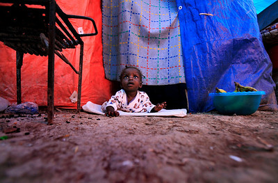 Judena Tal, a ten-month old baby, looks out from the entrance of her tent in a camp for earthquake survivors in Port-au-Prince, Monday, March 29, 2010.  A 7.0-magnitude earthquake hit Haiti on Jan. 12, killing and injuring thousands and leaving more than a million people living in makeshift camps. (AP Photo/Jorge Saenz)