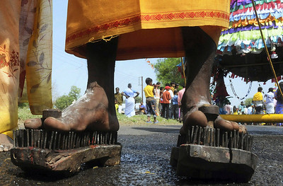 "A Tamil Hindu devotee wears nailed footwear during a religious procession during the ""Panguni Uthiram"" festival  in Bhopal, India, Monday, March 29, 2010. The Panguni Uthiram is an important Tamil festival observed in the Tamil month of Panguni (March – April), and celebrates the wedding of important deities in the Hindu religion. (AP Photo)"