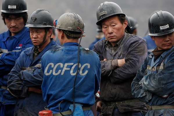 Mine workers look on as rescuers, unseen unload metal pipes at Wangjialing coal mine, Xiangning township, Shanxi province, about 650 kilometers (400 miles) southwest of Beijing, Monday, March 29, 2010.   Rescuers working in a drizzling rain raced Monday to free 153 coal miners trapped deep underground by a flood that may have started when workers digging a new mine in northern China accidentally broke into a network of old, water-filled shafts.  (AP Photo/Gemunu Amarasinghe)