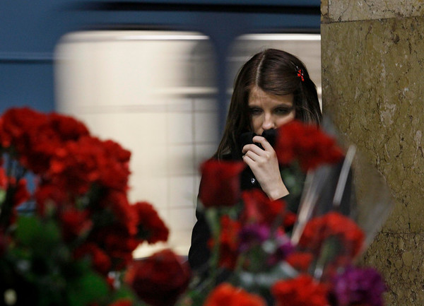 A woman grieves near the flower tributes placed in memory of the subway blasts' victims  at the Park Kultury (Park of Culture) subway station,  which was earlier hit by an explosion, Moscow, Monday, March 29, 2010. Two explosions blasted Moscow's subway system Monday morning as it was jam-packed with rush-hour passengers, killing at least 37 people, emergency officials and news agencies said. (AP Photo/Dmitry Lovetsky)