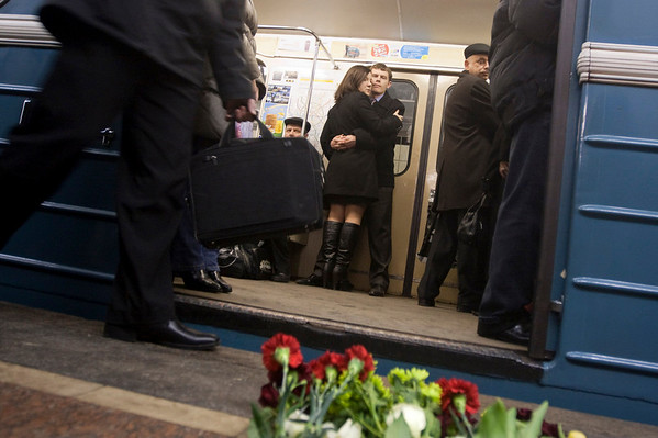 Commuters standing in a subway train's car look at the flowers laying at the Lubyanka Subway station, which was earlier hit by an explosion, in  Moscow, Monday, March 29, 2010. Two explosions blasted Moscow's subway system Monday morning as it was jam-packed with rush-hour passengers, killing at least 37 people, emergency officials and news agencies said. (AP Photo/Anna Shevelyova)