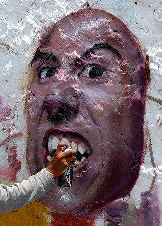 An artist works on a graffiti on a wall of the Azteca stadium in Mexico City, Sunday, April 18, 2010. The paintings are part of the 3rd Graffiti Contest organized by Mexico City's Secretary of Public Safety. (AP Photo/Marco Ugarte)