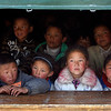 Tibetan children sit inside their temporary makeshift school as they wait for their class to start in earthquake-hit Yushu county, northwest China's Qinghai province, Monday, April 19, 2010. (AP Photo/Andy Wong)