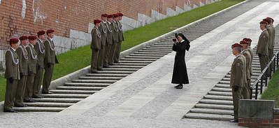 A nun photographs soldiers on Sunday, April 18, 2010  in Krakow, southern Poland.  The state funeral for late Polish President Lech Kaczynski in mostly Roman Catholic Poland began with a Mass at the 13th-century St. Mary's Basilica. The bodies of the first couple are carried in a funeral procession across the Old Town to the historic Wawel Cathedral, where they will be interred. Kaczynski, his wife Maria and other 94 people have been killed in a plane crash a week earlier. (AP Photo/Czarek Sokolowski)