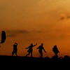 People are silhouetted as they have fun and kites are flown as the sun goes down on Hampstead Heath in London, Sunday, April 18, 2010.  (AP Photo/Matt Dunham)
