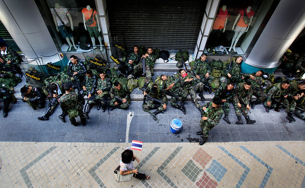 "Soldiers sleep on the sidewalk while a passerby walks past on Monday April 19, 2010 in Bangkok, Thailand.   Thai troops armed with assault rifles moved into Bangkok's central business district Monday morning to stop thousands of anti-government protesters and threatening to march down the capital's ""Wall Street.""  (AP Photo/Wong Maye-E)"