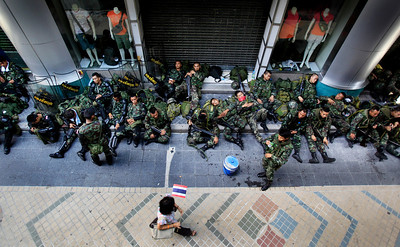 """Soldiers sleep on the sidewalk while a passerby walks past on Monday April 19, 2010 in Bangkok, Thailand.   Thai troops armed with assault rifles moved into Bangkok's central business district Monday morning to stop thousands of anti-government protesters and threatening to march down the capital's """"Wall Street.""""  (AP Photo/Wong Maye-E)"""