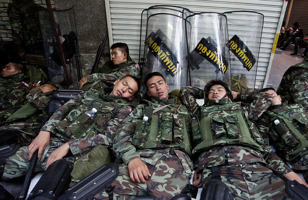 Thai soldiers sleep on Silom Road Monday, April 19, 2010, in the business district of downtown Bangkok, Thailand. Thai troops armed with assault rifles have moved to block Bangkok's prime business district not far from thousands of anti-government protesters.  The government already declared Silom Road, often called Bangkok's Wall Street, off-limits to the protesters who have occupied the main shopping district nearby for weeks. (AP Photo/David Longstreath)