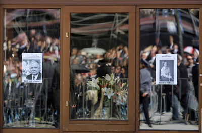 Pictures of Late Polish President Lech Kaczynski and his wife Maria are seen as people wait for a mass to be celebrated for victims of the Smolensk plane crash in Krakow, Poland Sunday, April 18, 2010. Polish President Lech Kaczynski and his wife, Maria Kaczynska who were killed in a plane crash in Russia are to be buried after a state funeral at Krakow's Wawel Cathedral. (AP Photo/Petr David Josek)