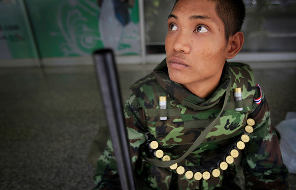 "A soldier rests on a street on Monday, April 19, 2010, in Bangkok, Thailand. Thai troops armed with assault rifles moved into Bangkok's central business district Monday morning to stop thousands of anti-government protesters threatening to march down the capital's ""Wall Street.""  (AP Photo/Wong Maye-E)"