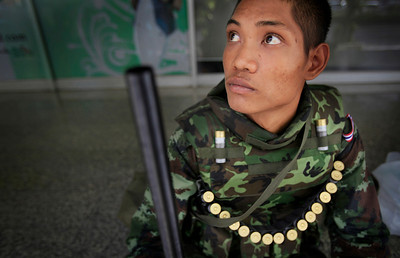 """A soldier rests on a street on Monday, April 19, 2010, in Bangkok, Thailand. Thai troops armed with assault rifles moved into Bangkok's central business district Monday morning to stop thousands of anti-government protesters threatening to march down the capital's """"Wall Street.""""  (AP Photo/Wong Maye-E)"""