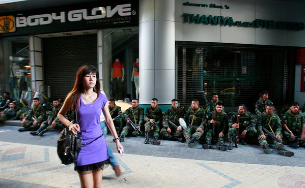 APTOPIX_Thailand_Politics_B.JPG An office worker walks past soldiers resting on a roadside of the business district Monday, April 19, 2010, in Bangkok, Thailand. Thai troops armed with assault rifles moved into positions early Monday to block Bangkok's prime business district from thousands of anti-government protesters who have threatened to enter. (AP Photo/Apichart Weerawong)