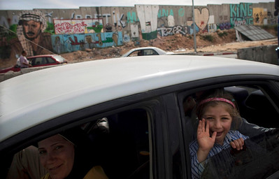 A Palestinian girl waves from the car as they wait to cross at the Kalandia checkpoint between the West Bank city of Ramallah and Jerusalem, Sunday, April 18, 2010. (AP Photo/Maya Hitij)