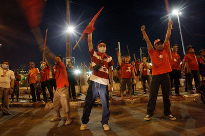 Thai anti-government protesters raise flag poles into the air as they confront Thai police, unseen in the photograph, who blocked the street in downtown Bangkok in the early morning hours of Monday April 19, 2010. (AP Photo/David Guttenfelder)