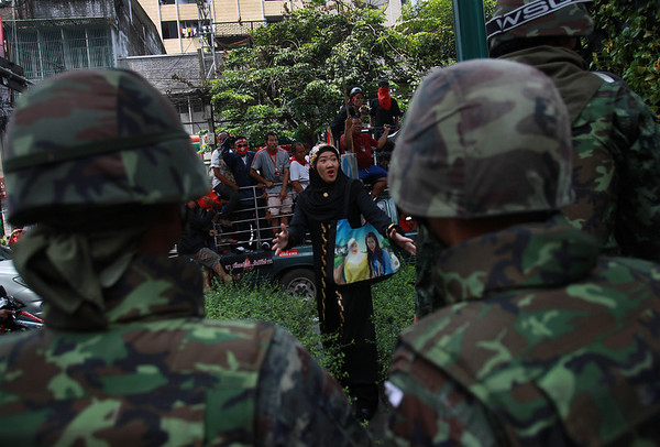 "A Thai woman and ""Red Shirts"" protesters confront Thai soldiers on a street in Bangkok, Sunday April 25, 2010. Thailand's embattled Prime Minister Abhisit Vejjajiva acknowledged he initially underestimated the protesters who have occupied central Bangkok for weeks, but he offered no initiatives Sunday to end the country's prolonged, sometimes bloody political crisis. (AP Photo/David Guttenfelder)"