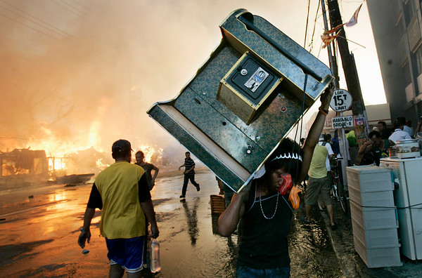 A resident carries a karaoke machine to safety as fire guts shanties at a slum area in suburban Quezon City, north of Manila, Philippines, Sunday, April 25, 2010. Metro Manila fire marshal Pablo Cordeta said that about 300 shanties were affected leaving some 1,500 families homeless. (AP Photo/Aaron Favila)