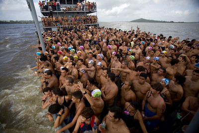 "wimmers are driven on a boat to the start point of the ""Swim across the Orinoco and the Caroni rivers race"" in San Felix, southern Venezuela, Sunday, April 25, 2010. About 900 swimmers took part in the 1.9 mile annual race across one of the largest rivers in the world, the Orinoco. (AP Photo/Ariana Cubillos)"