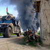 Afghan security forces mans on the scene as trucks arrying supplies to coalition forces burn after hundreds of people blocked a main road and set them on fire to protest what they said were civilian deaths in NATO operations in Logar province, west of Kabul, Afghanistan, Sunday, April 25, 2010. They gathered hours after NATO said coalition troops killed several insurgents and captured a Taliban sub-commander. (AP Photo/Mohammed Obaid Ormur)