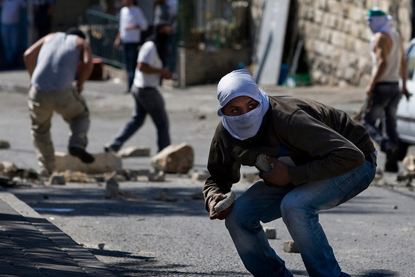 Masked Palestinian youths hurl stones at Israeli police, not seen, during clashes in the east Jerusalem neighborhood of Silwan, Sunday, April 25, 2010. Palestinian protesters burned tires and garbage and threw rocks and two firebombs at Israeli police as three dozen ultranationalist Jews, carrying Israeli flags, marched on Sunday through the east Jerusalem neighborhood of Silwan to dramatize their claims to the eastern sector of the contested holy city. (AP Photo/Sebastian Scheiner)