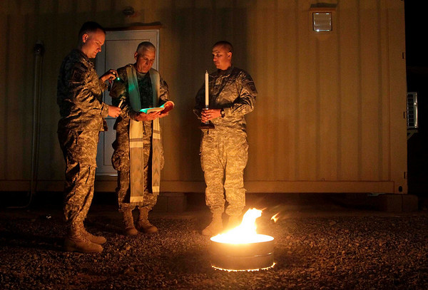 United States Army Capt. Ryan Kenny, of Billings, Mont., left, with the 82nd Airborne Division, holds a light over the text for Chaplain William Kneemiller, center, as he reads while Staff Sgt. Richard Webb, of Donna, Texas prepares to light the Easter candle during the Lighting of the Easter Vigil fire service of light, Saturday, Aug. 3, 2010 at a forward operating base in the Arghandab Valley of Kandahar province in Afghanistan. (AP Photo/Julie Jacobson)