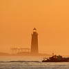 A lobster boat passes Ram Island Ledge Light at dawn, Friday, April 2, 2010, off Cape Elizabeth, Maine. A forecast for several days of warm, dry weather will bring relief to New England, which received record rainfall in March. (AP Photo/Robert F. Bukaty)