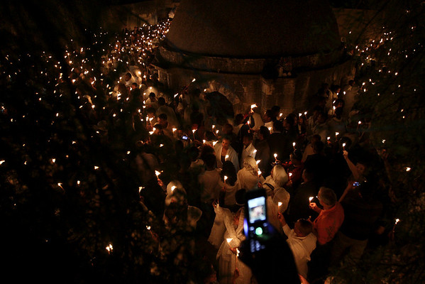 An Ethiopian Orthodox Christian pilgrim takes a picture with his cell phone as the procession of the Holy Fire at Deir El Sultan in the Church of the Holy Sepulcher, believed by many to be the site of the crucifixion takes place below him, in Jerusalem's Old City, Saturday, April 3, 2010. Orthodox Christians are marking the solemn period of Easter. (AP Photo/Tara Todras-Whitehill)