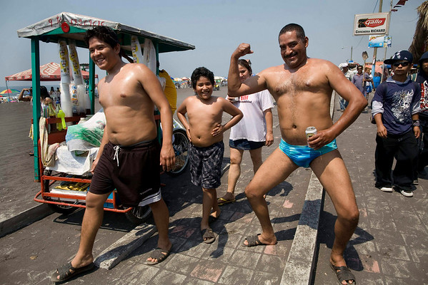 People pose for pictures during Holy Week holidays in a public beach of Puerto San Jose, some 60 km south of Guatemala City, Saturday, April 3, 2010. (AP Photo/Rodrigo Abd)