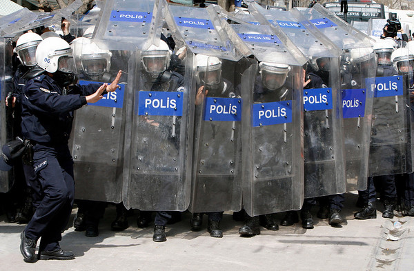 Riot police take cover behind their shields as they clash with Turkish workers of the state tobacco company TEKEL,  who are protesting layoffs and the government's labor policy for second day in Ankara, Friday, April 2, 2010.  More than 5,000 riot police have been deployed in the center of Turkish capital to police the demonstration by some  hundreds of workers. (AP Photo/Burhan Ozbilici)