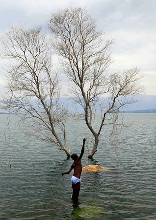A youth fishes in Lake Azuei near the border with the Dominican Republic in Malpasse, Haiti, Thursday, April 1, 2010.  Fish from Lake Azuei sell for 50 cents at local street markets. (AP Photo/Jorge Saenz)