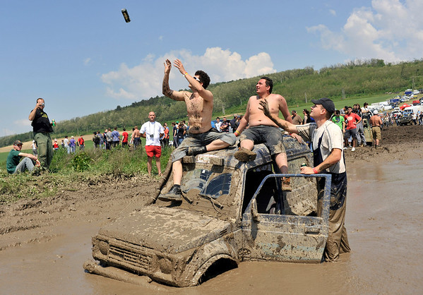 Drivers receive a can of beer as they wait with their off-road vehicle stuck in mud during the annual Somogybabod International Off Road Festival in Somogybabod, Hungary, ON Saturday, May 22, 2010.  Environmentalists call to ban the annual off-road event, claiming that the hundreds of 4X4 vehicles destroy the forest area close to the Lake Balaton, Hungary's largest water and tourist resorts. (AP Photo/Bela Szandelszky)