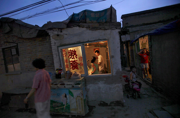 A Chinese man, and his daughter, center, works in their restaurant, while children look on from an alley in a neighborhood in Beijing, China, Sunday, May 23, 2010. (AP Photo/Muhammed Muheisen)