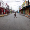 A man walks  in an empty street in downtown Kingston, usually packed with cars and people during a normal day, Wednesday, May 26, 2010.  According to the the country's official ombudsman, at least 44 civilians have been killed as Jamaican security forces have moved into the slum stronghold of a gang leader sought by the U.S. justice yet he remains at large after nearly 3 days of street battles.(AP Photo/Rodrigo Abd)