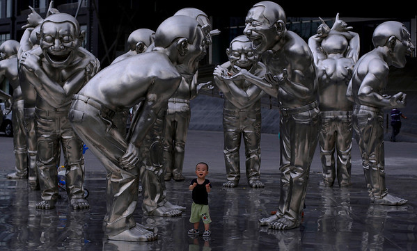 A Chinese child reacts while playing between sculptures outside a museum in Beijing, China, Wednesday, May 26, 2010. (AP Photo/Muhammed Muheisen)