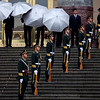 A Chinese agent, standing in front of a pillar, looks on near members of an honor guard while ushers prepare umbrellas before a welcome ceremony for visiting Indian President Pratibha Patil at the Great Hall of the People in Beijing Thursday, May 27, 2010. (AP Photo/Alexander F. Yuan)