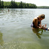 Tarun Fehsenfeld, of Acton, Mass., supports 10-month-old Elliot in the water at Walden Pond, in Concord, Mass., Wednesday, May, 26, 2010.  Heavy spring flooding has forced the state to cut summer access by nearly half at Walden Pond, state officials said Wednesday. The site was made famous by author Henry David Thoreau. (AP Photo/Steven Senne)