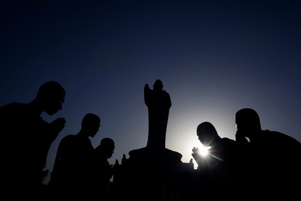 Buddist monks offering prayers to a Buddha statue are silhouetted against the setting sun on the occasion of Buddha Poornima in Hyderabad, India, Thursday, May 27, 2010. Buddha Poornima commemorates the birth, enlightenment and demise of Buddha. (AP Photo/Mahesh Kumar A.)