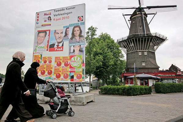 Two veiled women pass campaign posters for the upcoming June 9national elections in Amsterdam on Thursday May 27, 2010. For a decade, the Netherlands has been at the forefront of a Europe-wide crackdown on immigration and the debate over a perceived failure of Muslims to integrate. With national elections less than two weeks away, issues like banning burkas and mandatory citizenship classes for immigrants have been shouldered aside in favor of the debate over how to balance the budget. All political parties are pledging spending cuts, and whatever the result, the average Dutchman is likely to see his government-funded comfort zone shrink. (AP Photo/Peter Dejong)