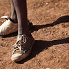 In this photo taken Tuesday May 25, 2010, a child with mismatched shoes waits to play a soccer match at the Matikiring sports ground, near Lichtenburg, in the rural part of northern South Africa. Outsiders are rare as rain in this dusty corner of northern South Africa. So when cars carrying government workers, flags and a sound system arrived at the community sports field, curious villagers streamed in. (AP Photo/Denis Farrell)